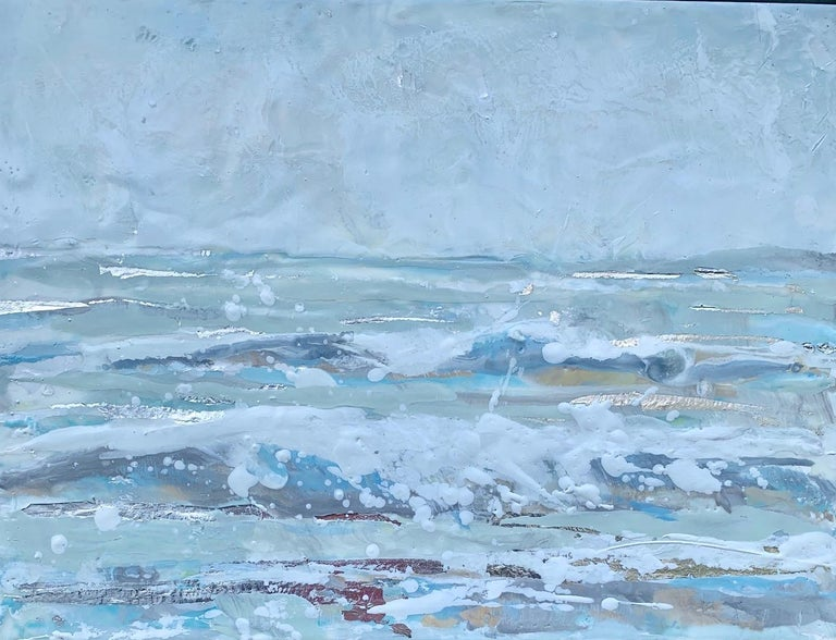 'Salt Spray' is a small silver framed encaustic on board seascape painting created by American artist Maureen Naughton in 2019. Featuring a delicate palette made of grey, white, soft blue, brown and purple tones, the painting depicts foamy waves
