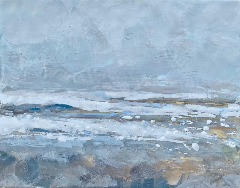 'Salt Tipped' is a small silver framed abstract encaustic on board seascape painting created by American artist Maureen Naughton in 2019. Featuring a delicate palette made of grey, white, brown, gold and soft blue tones, the painting, leaning