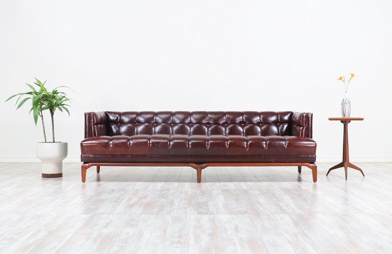 Fabulous biscuit tufted leather sofa designed by Maurice Bailey for Monteverdi-Young of Beverly Hills in the 1960s. This comfortable sofa is newly reupholstered in a full grain brown leather and set on a carved solid walnut wood base. Meticulously