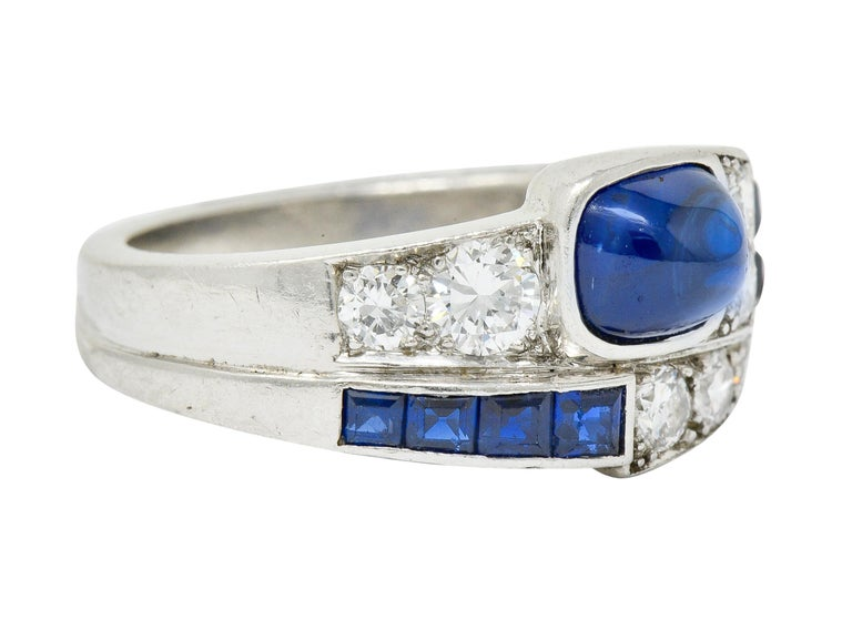 Designed as a unique faux bypass style band  Centering a cushion sugarloaf cabochon sapphire weighing approximately 1.65 carats  Medium-dark royal blue in color and well-matched to square cut sapphire accents weighing approximately 0.32 carat