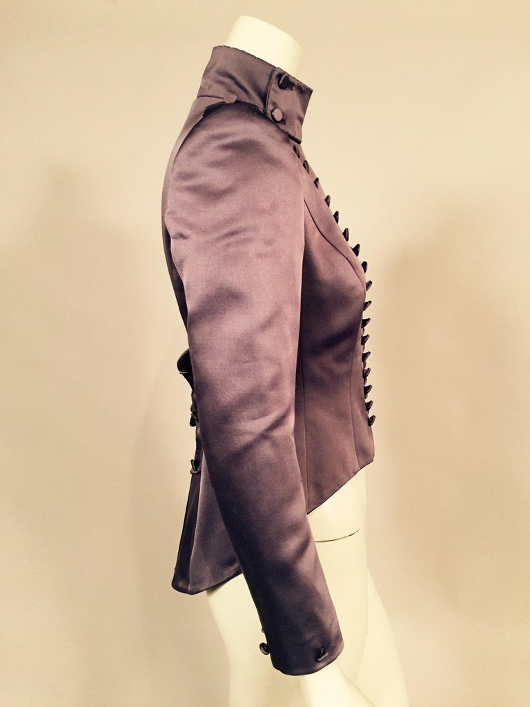 Mauve silk satin enhances the Victorian look of this very contemporary jacket designed by Maggie Norris Couture in New York City. The jacket has a high collar, sixty hand covered silk buttons, countless embroidered French knots, epaulets and avery