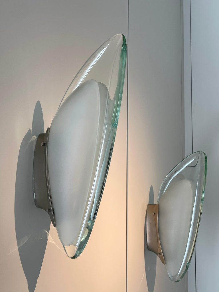 Pair of wall lamp by Max Ingrand for Fontana Arte Italy, 1965. Shell made of a thick slightly green tinted glass and two sandblasted glass lobes, nickel-plated brass plate, accommodating three small lights. Excellent vintage patina.