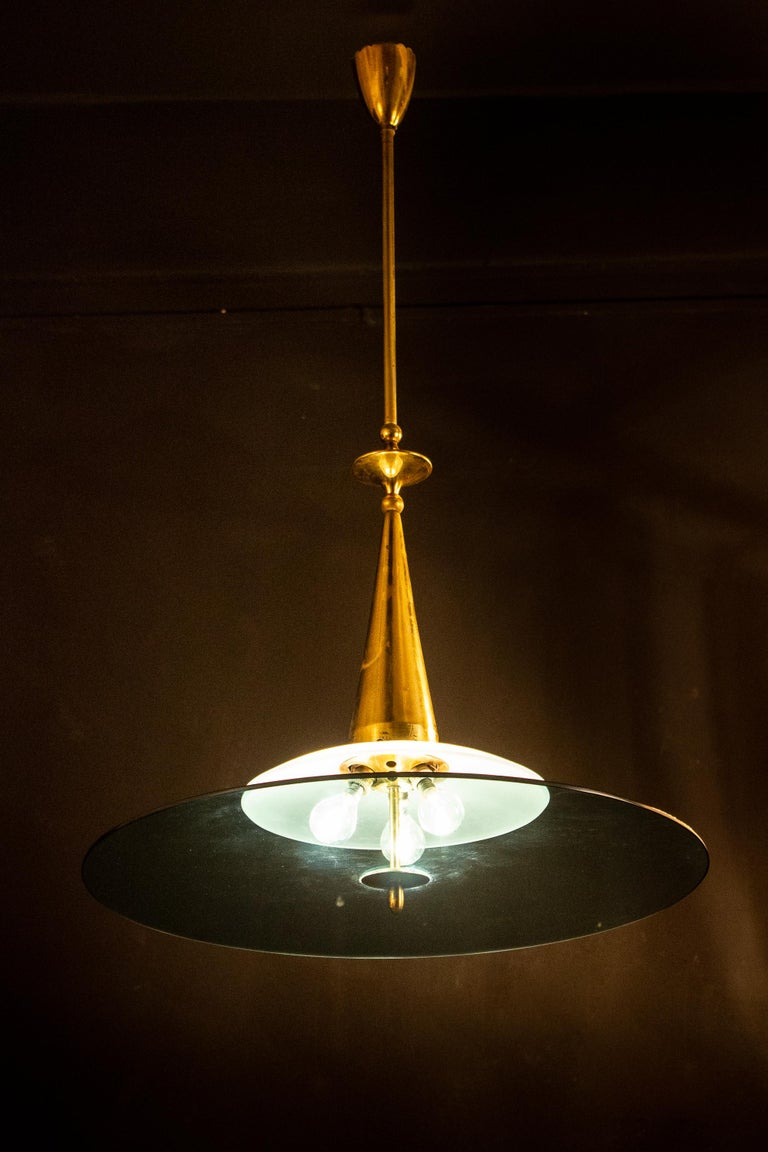 Elegant Minimalist chandelier attributed to Max Ingrand for Fontana Arte, with a frosted glass bowl and a large blue crystal shade supported by sophisticated polished brass hardware. The glasses are in perfect condition. Three E 14 lightbulbs. We