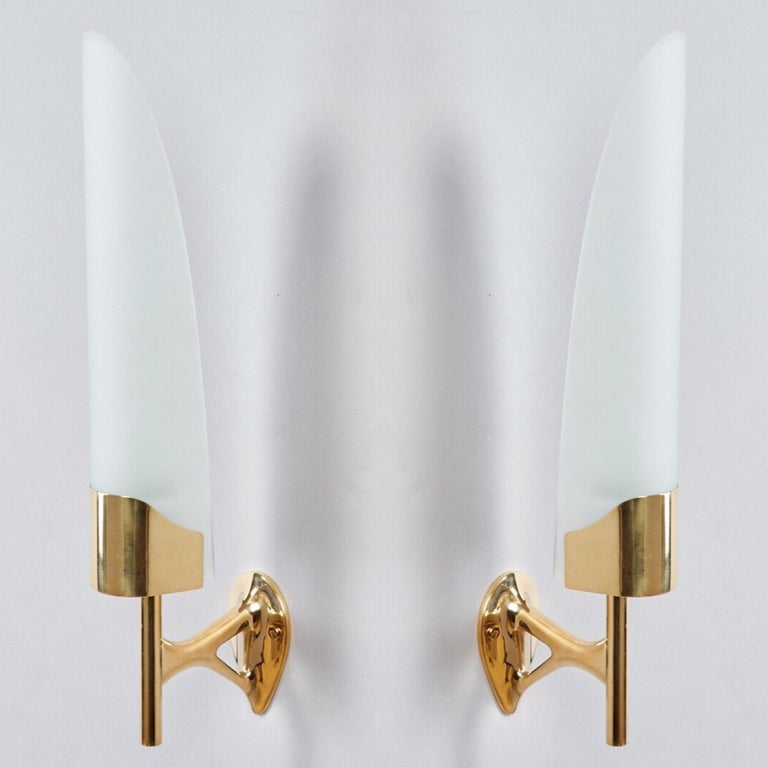 Max Ingrand (1908-1969)   A beautiful pair of long, curved frosted glass sconces on sculptural projecting mounts with elegant keyhole detail, in polished brass, by Max Ingrand for Fontana Arte.   Italy, 1950's.   Measures: 16