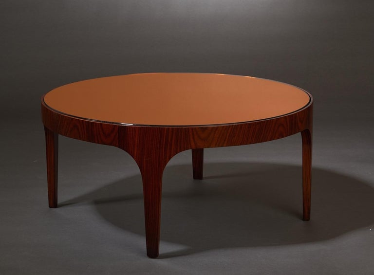 Max Ingrand (1908 - 1969)  A rare and exceptionally pure Model 1774 round coffee table by Max Ingrand for Fontana Arte. In rosewood with a circular top in burnt umber mirrored glass, resting on an elegantly curved base raised on tapering legs.