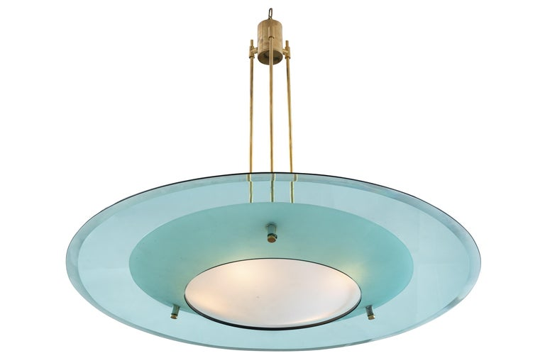 Fontana Arte chandelier model 2097 designed by Max Ingrand. It features a light blue concave beveled glass disc with a conical frosted glass shade in the center. The frame is solid brass.