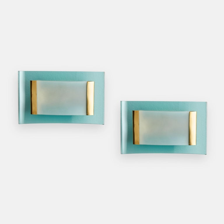 Max Ingrand for Fontana Arte rare and exquisite pair of modernist sconces with light blue bent cut and bevelled glass and smaller bent frosted glass held by brass fittings.  Literature: Illuminazione Arredamento Cristalli d'Arte,