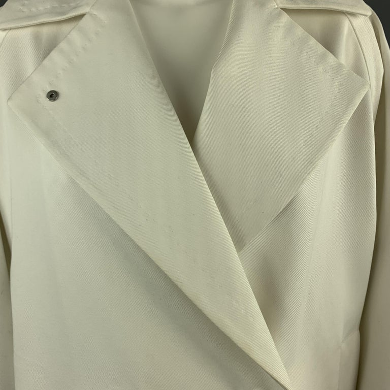 MAX MARA coat comes in off white cotton twill with a pointed lapel, hidden snap double breasted front, raglan sleeves, and elastic drawstring hem. Minor discolorations throughout. As-is.   Very Good Pre-Owned Condition. Marked: USA
