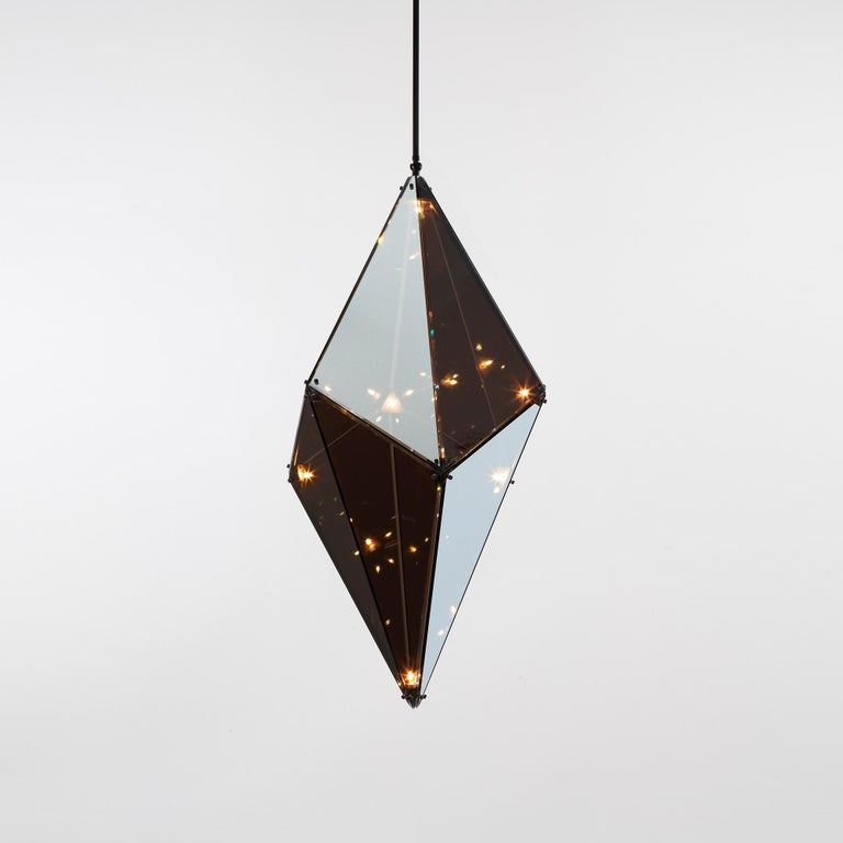 Bec Brittain's Maxhedron is a study in material transformation through light and reflection. When off, the partly-translucent Maxhedron reflects and blends with its environment; when on, the dazzling inner constellation of bulbs projects bands of