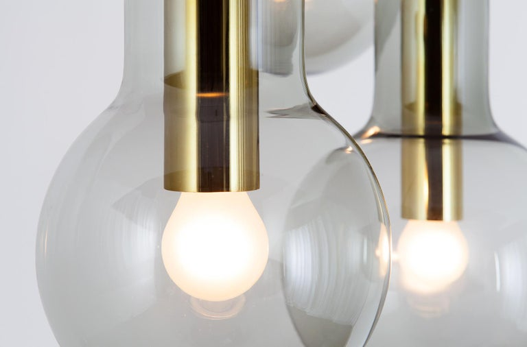 Set of 3 lamps (s, m and l). Light smoked glass with brass colored metal socket. Excellent condition.   In the early 1960s, RAAK produced these extraordinary pendants, named according to the logic of their striking design. The shape of the pendant