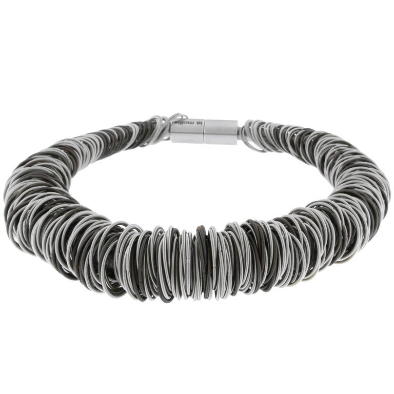 Balanced between the exotic and the industrial, the Maxi One stainless steel necklace is strikingly elegant. The hardness of steel is softened by a clever structure of elastic hoops of finely spun springs, some plated with gold. By transforming an