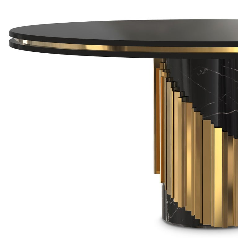 Table maxima round with wooden black lacquered top with polished brass rim around. On black marble base with polished brass rods around the base.
