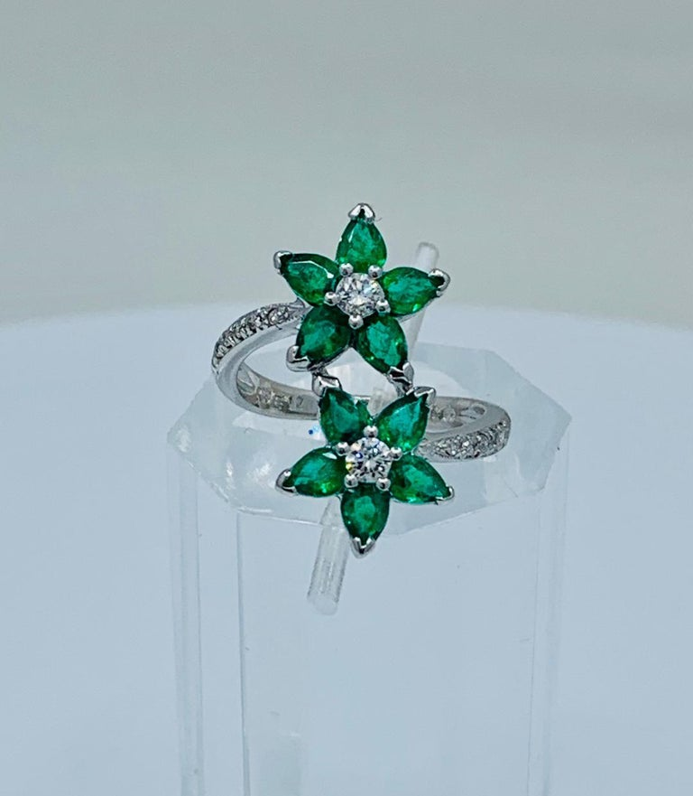 Very feminine custom made estate wrap-around ring features prong set, pear cut emerald petals which form a pair of flowers accented with round brilliant white diamond centers. Diamond pave stems run half way down the shank of the ring on both