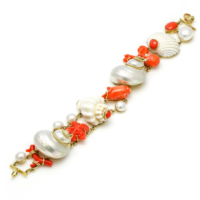 Mazza Company shell, coral, diamond and pearl sea life charm bracelet in 18k yellow gold from the Grotto collection. Size, medium. Lobster clasp.  Width, 25mm Height, 21mm Weight, 50.5 grams Carat Weight, .05 carat