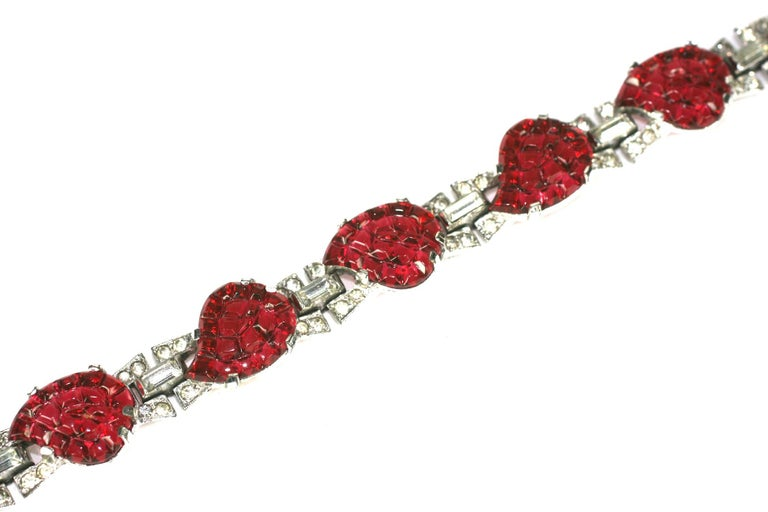 Mazer Art Deco faux ruby leaves invisibly set link bracelet of rhodium plated base metal,  small crystal rhinestone pave,  and eight faux invisibly set calibre pressed ruby glass. The non-use of Sterling dates this to 1938  through 1942. Excellent