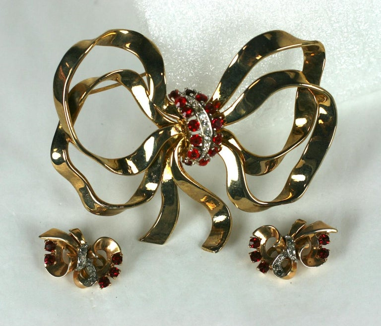 Mazer Retro massively scaled bow Retro knot brooch and matching ear clips. The multi loop bow and ear clips of 14 KT yellow gold plate with crystal rhinestone pave and faux round faceted rubies.  1940's USA.  Excellent Condition, Signed Mazer.