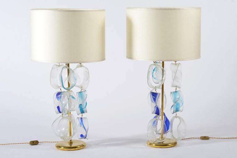 Pair of Murano glass table lamps made by the Mazzega manufactory with chains in transparent glass and blue brass. The shades are new in light beige silk. The measures are with lampshades. Italia midcentury, 1960.