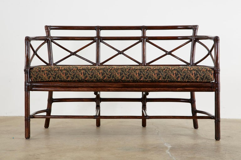Genuine McGuire organic modern Gondola settee or bench crafted from bamboo rattan poles by McGuire. Designed by Elinor McGuire and inspired by Venetian gondolas in Italy. The frame has gracefully curved ends with X motifs in the back. The exposed