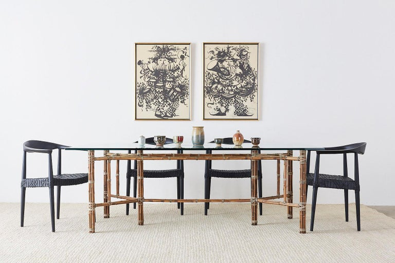 Stunning organic modern dining table made by McGuire. Features a large iron frame wrapped with bamboo rattan split poles and reinforced with leather rawhide laces. Topped with a large pane of thick beveled glass. The base measures 73 wide by 31