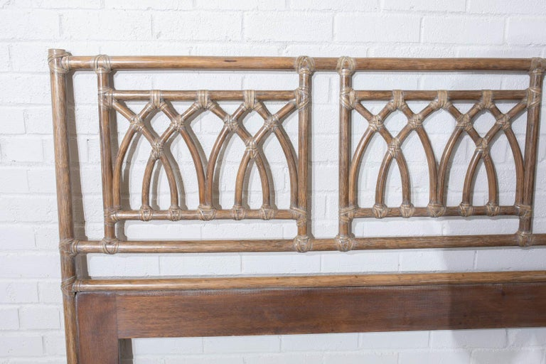 Organic modern style headboard made by McGuire. Features a frame constructed from bamboo rattan poles lashed together with leather rawhide strapping. The frame is decorated with cathedral arch motif in a geometric design. Appears new with no
