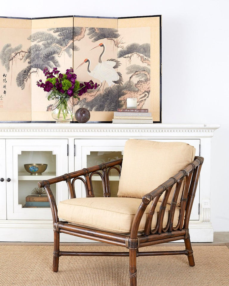 Genuine McGuire organic modern lounge chair or armchair constructed from thick bamboo rattan poles. The frame features an open design with decorative round windows on the sides and back. Reinforced with leather rawhide laces on the exposed joints.