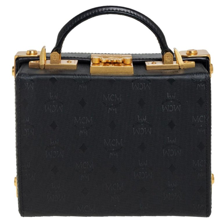 Adorned with decorative gold-tone accents on the exterior, this Berlin Box bag from MCM has a structured shape and a refined style. The bag comes crafted from black Visetos canvas as well as leather and flaunts a top handle and a shoulder strap. The