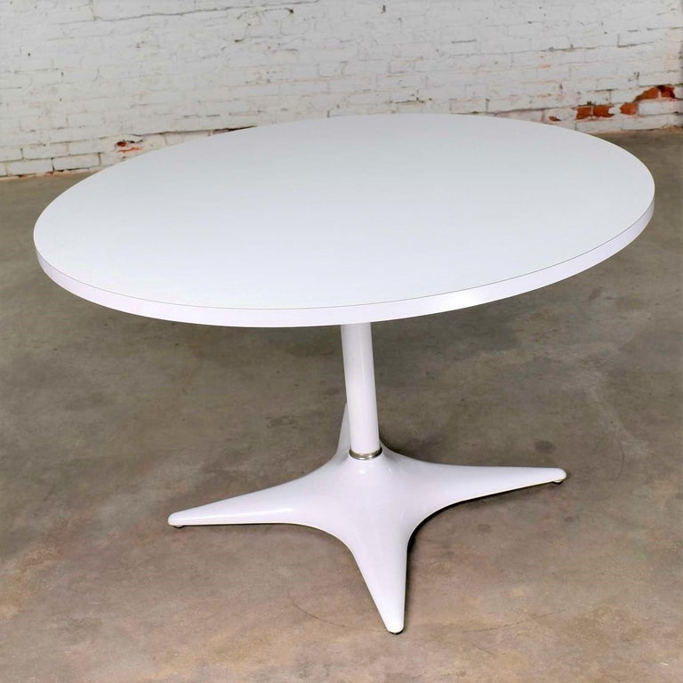 Handsome Mid-Century Modern (MCM) white round pedestal dining table with a white enameled shaft and four-star base with a white laminate top by Brody Furniture Chicago. It is in wonderful vintage condition with no outstanding flaws we have seen.