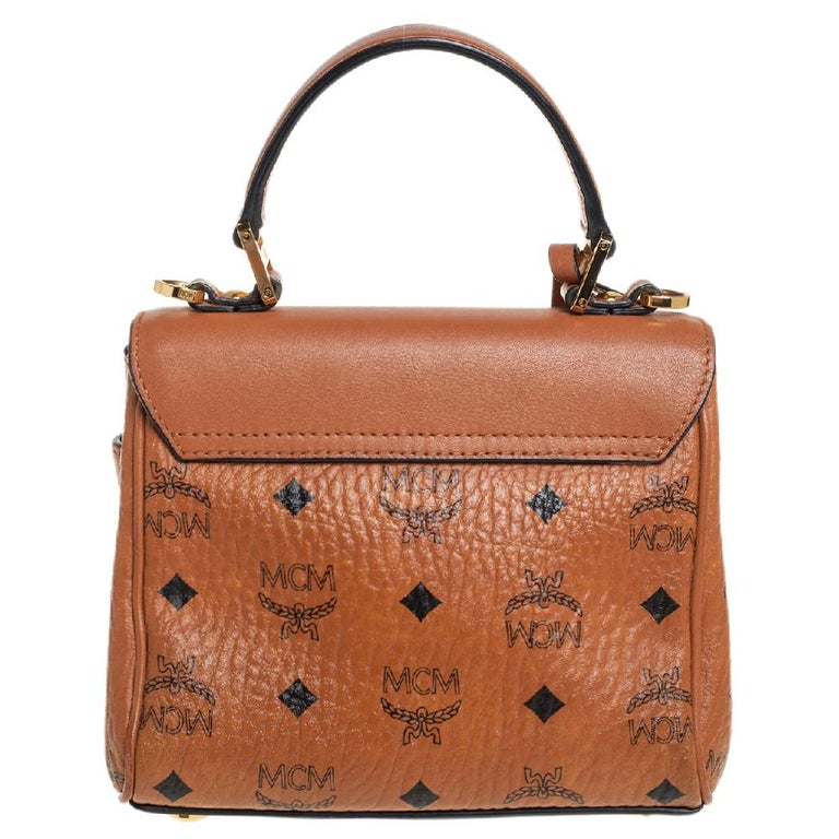 This stunning Mini Heritage bag in Visetos canvas and leather is from MCM's prized collection of handbags. It features a single top handle, a twist-lock closure on the front flap, and a fabric-lined interior. It is detailed with gold-tone hardware
