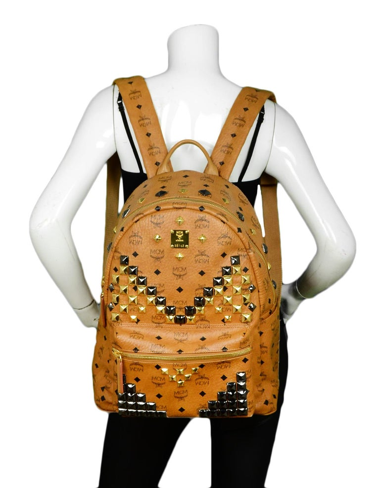MCM Tan Monogram Star M Stud Large Backpack  Made In: Korea Color: Tan Hardware: Goldtone  Materials: Leather Lining: Fine leather textile Closure/Opening: Top zip pocket  Exterior Pockets: Front zip pocket, two flat pockets Interior Pockets: Two
