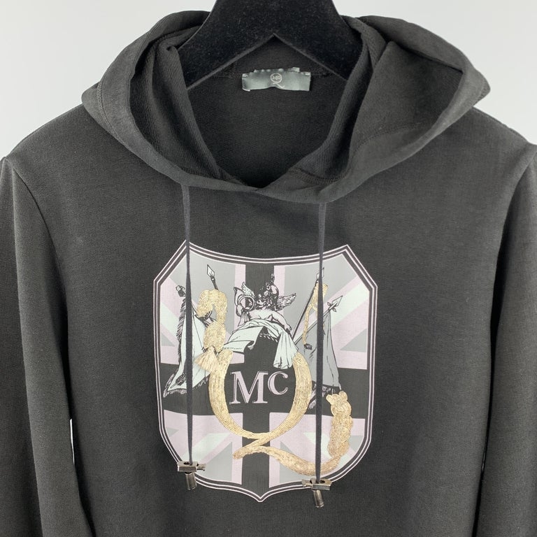 MCQ by ALEXANDER MCQUEEN sweatshirt comes in a solid black cotton material, featuring a hood, a graphic and embellishment at chest, silver tone metal hardware, and ribbed cuffs and hem. Made in Italy.  Very Good Pre-Owned Condition. Marked: US