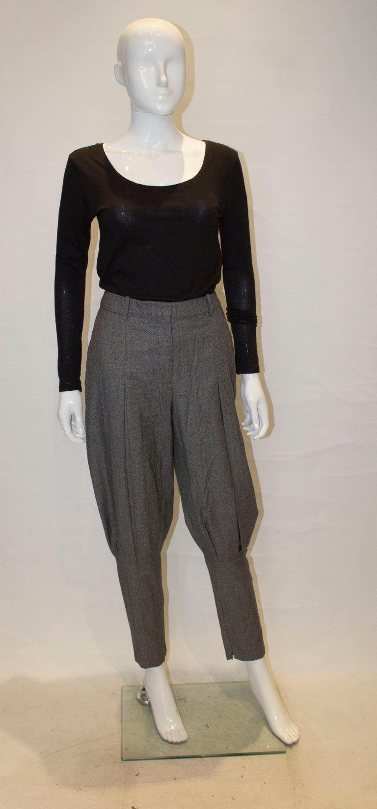 An elegant and unusual pair of trousers by McQueen.  The trousers are in an interesting wool  and have two front pockets, sewn down pleats at the front and gathering under the knee. The trousers have belt hoops and inner calf zips.