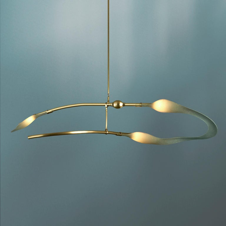 The McTavish is a chandelier featuring smooth, floating brass and undulating sea-colored fiberglass.  It's a horizontal chandelier ideal for dining rooms, living rooms and can be installed as multiples in larger spaces.  The chandelier is part of
