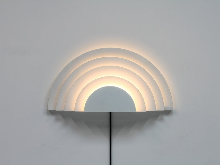 A meander wall sconce designed by Cesare Casati and Emanuele Ponzio for RAAK in the 1970s. RAAK was a leading Dutch light manufacturer of the period.  Consisting of six-layered semi-circles of white lacquered metal which emit a warm glow when lit