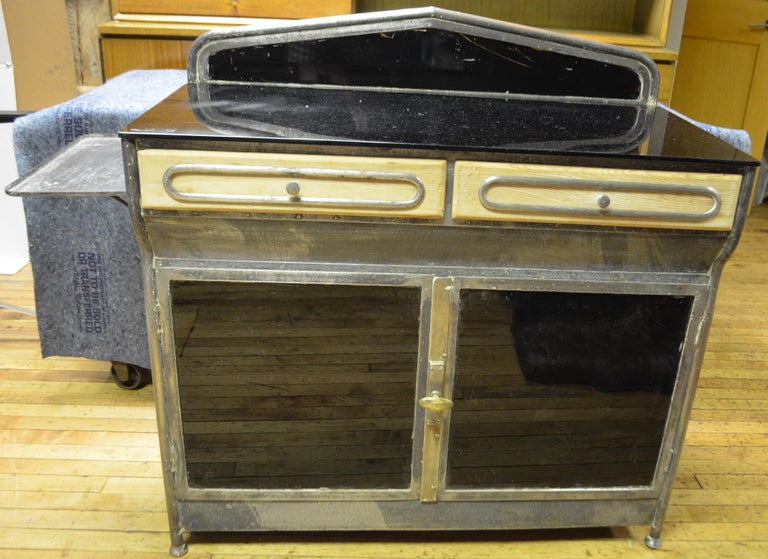 Medical cabinet, Art Deco, circa 1920s. Dark glass mirrors as back splash, counter top and bottom storage doors. Two wooden drawers with steel filagree design and steel shelf on left-hand side. Bottom cabinet offers additional storage. Ideal