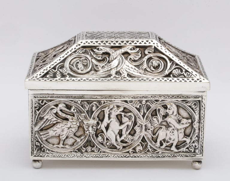Medieval-style, sterling silver (.950) casket - form jewelry box with hinged lid, having bun feet, Paris, circa 1900. Suede lined. Designed with mythical birds and scenes. Measures 4 3/4 inches high (at highest point) x 6 inches wide x 3 3/4 inches