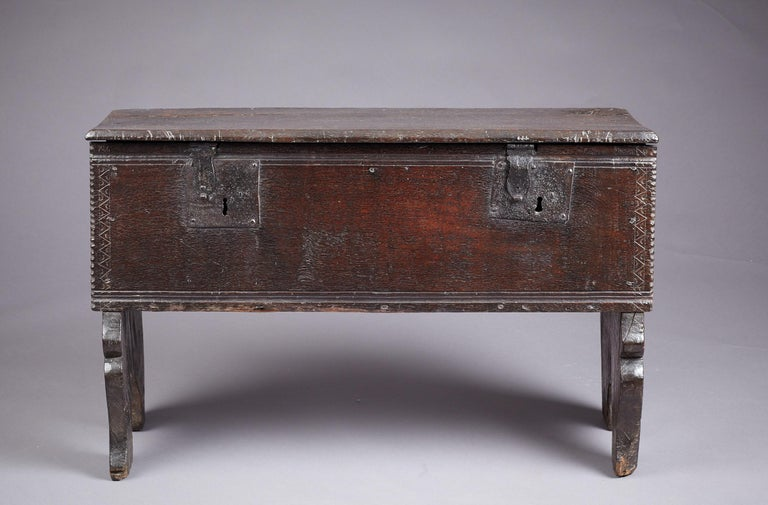 Medieval - Tudor oak boarded / plank chest, Henry VII / Henry VIII period, English, circa 1480-1530.  The plank lid with chamfered edges above a twin moulded, chip carved and chevron incised front panel with original twin locks, joined by bold arch