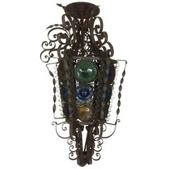 Mediterranean Style Iron Light Fixture with Curly Cues and Colored Glass