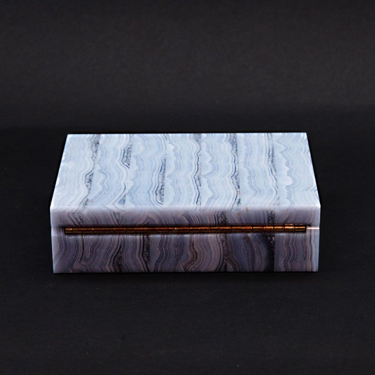 Blue lace agate box with light blue and white and translucent stripes. Fine black felt interior and gold tone hardware. Said to be a relaxing stone because of cool hues. Some healers say that the blue lace agate improves communication.  Measures: