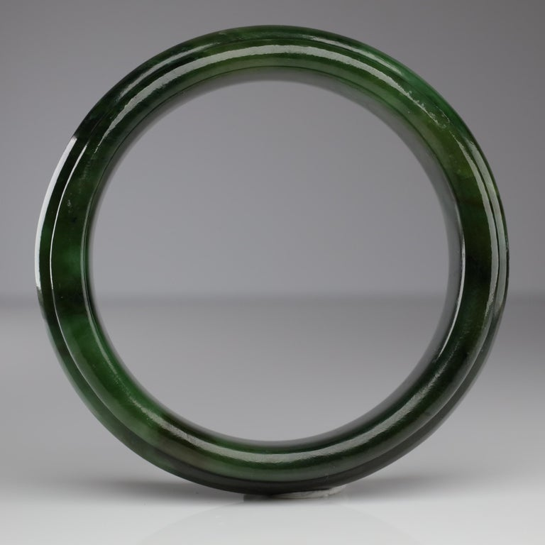 Here we have medium-large *heavy* bangle hand-carved from a solid piece of Wyoming nephrite jade. The unusual carving features a raised beveled
