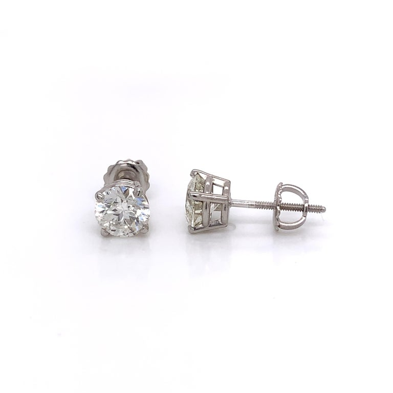 2.06 Carat diamond stud earrings made with real/natural brilliant cut diamonds. Total Diamond Weight: 2.06 carats. Diamond Quantity: 2 round diamonds. Color: G-H. Clarity: SI2-SI3. Mounted on 18 karat white gold screw back setting.