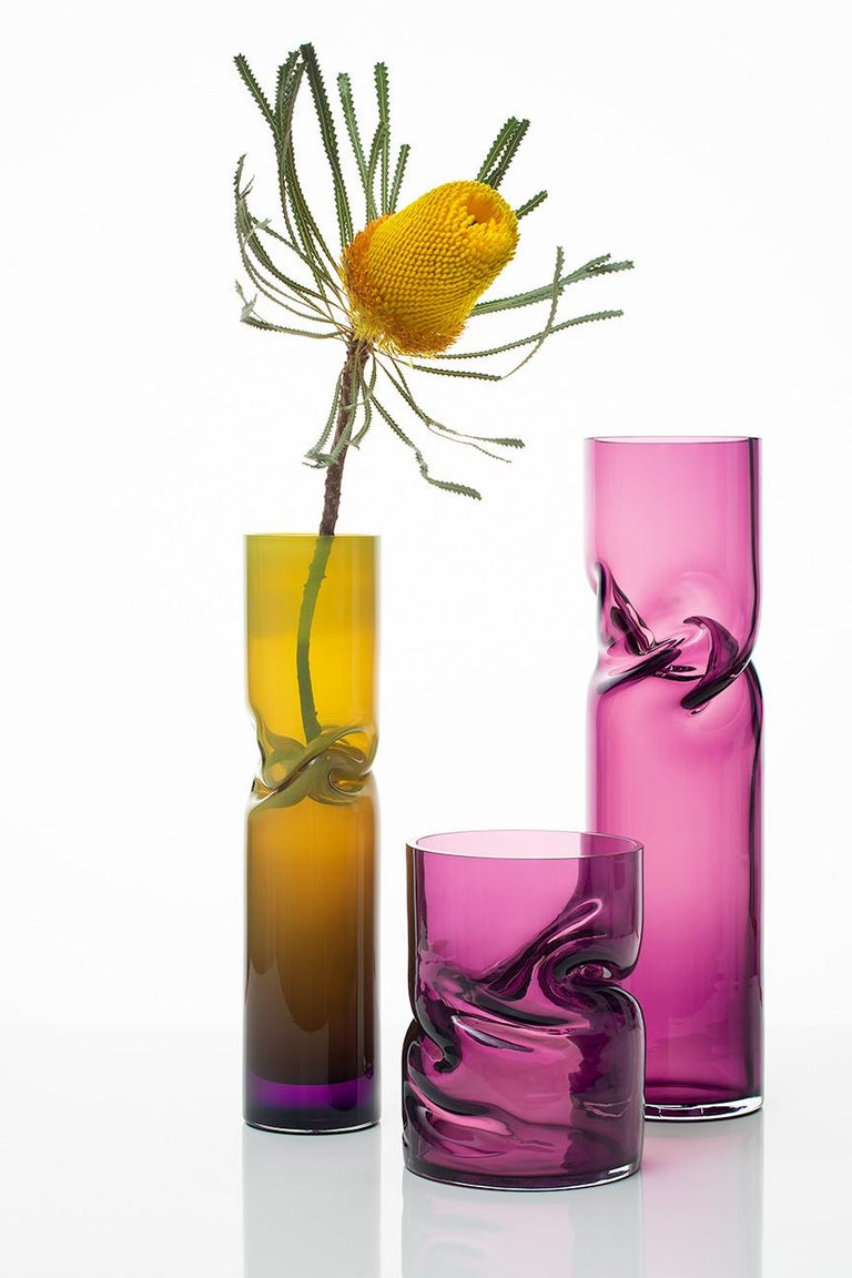 During the glass blowing process, vases are twisted and shaped to produce crushed forms within the confines of a simple geometric framework. Each piece is unique by Virtue of the making process.