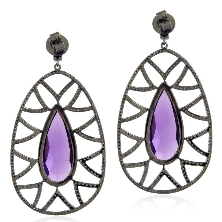 Bold and distinctive, these statement-making Bora Bora earrings are stunningly set in semi precious gems. The drops of faceted amethyst are framed by diamond pave arches. The negative space accentuates the main stone to create a dazzling dangle.
