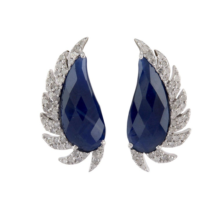 These distinctive stud earrings are modern twist to fine jewelry, handcrafted in 14K gold, sterling silver, blue sapphire and diamonds. The iridescent 16.0-ct rose cut blue sapphire is surrounded by 0.67-ct signature diamond pave arches. A fusion