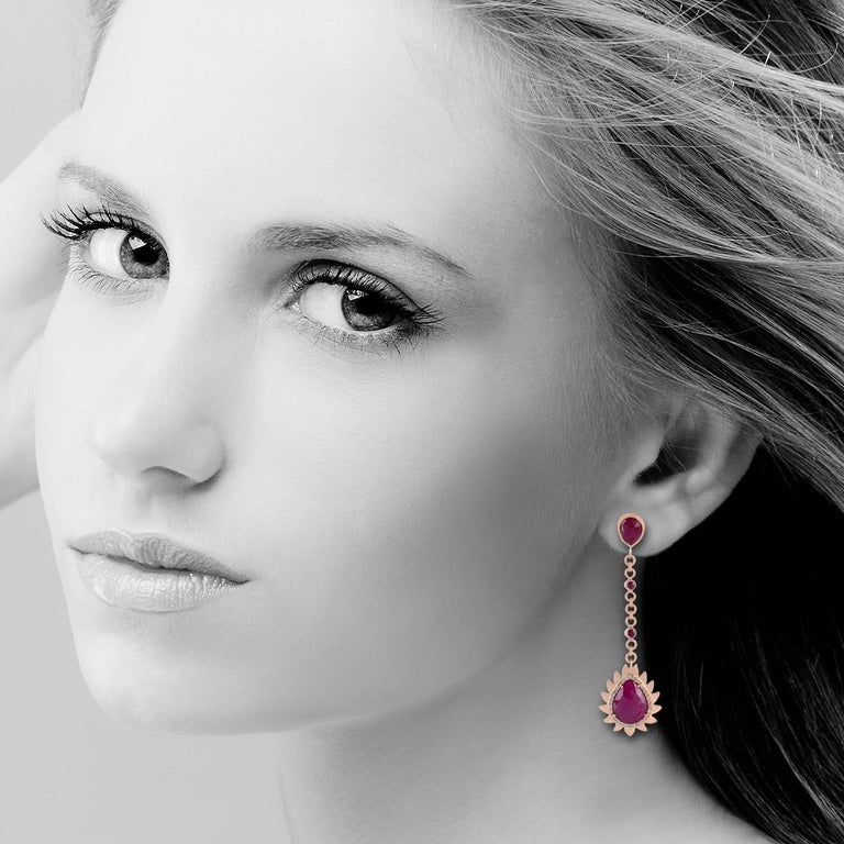 These modern gorgeous flame drop earrings are handcrafted in 18K gold, sterling silver, rubies and diamonds. Exquisitely framed in