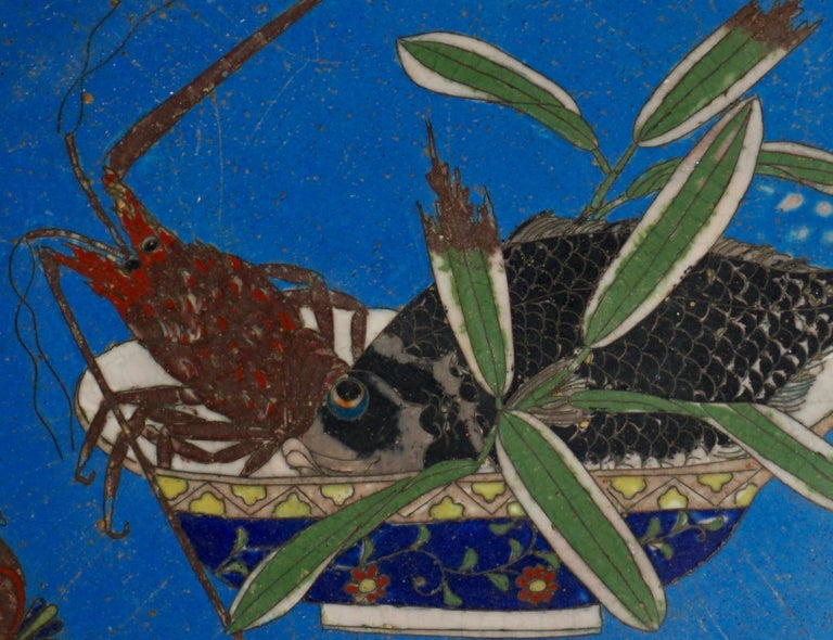 A early and exquisite Japanese Cloisonne platter in rare lapis lazuli cobalt blue background with a seafood bowl filled with a carp fish and a lobster. The lobster and fish have eye balls looking at a dragonfly that is sitting on the lobsters