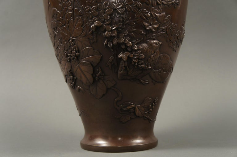 Meiji Japanese bronze vase with grasses and Quail design, Meiji period (1868-1912) bronze vase with elaborate raised design of wild grasses, flowers, and vine partially hiding a pair of quail. Beautiful composition. Artist seal on the bottom in the