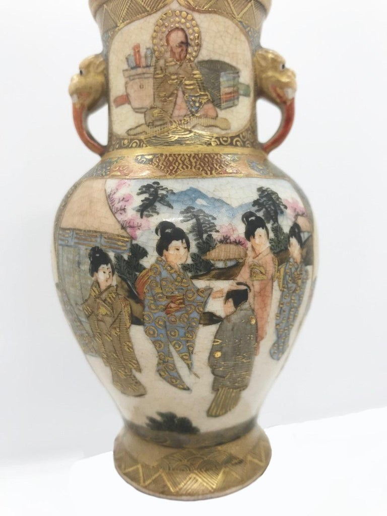 This is an exquisite miniature Japanese Satsuma vase from the Meiji period (1868-1911). It is superbly decorated with various shaped figures in cartouches in front and on the reverse on a brocade patterned base. Two Foo dog handles are applied. It