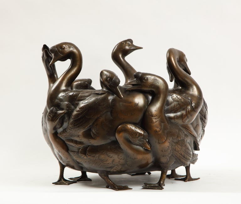 A very rare 19th/20th century Japanese bronze centerpiece of a flock of geese with heads cast in three dimensions, stamped and signed Gen Ryusai Seya. Each having gold inlaid eyes with all sections of their bodies hand-chassed with the finest