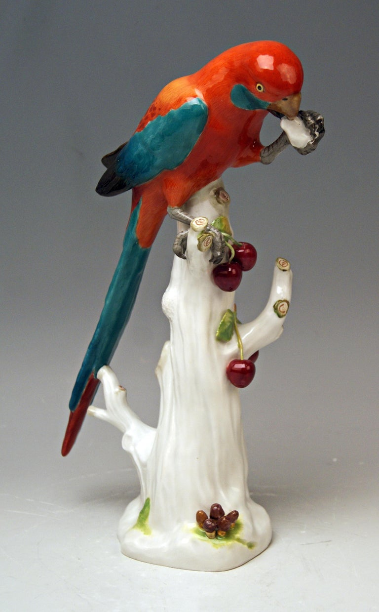 Animal figurine: Parrot situated on a tree's stump with cherries  Manufactory: Meissen Hallmarked: Blue Meissen sword mark with pommels on hilts (underglazed) model number 20x / painter's number 72 / former's number 6 First quality Dating: