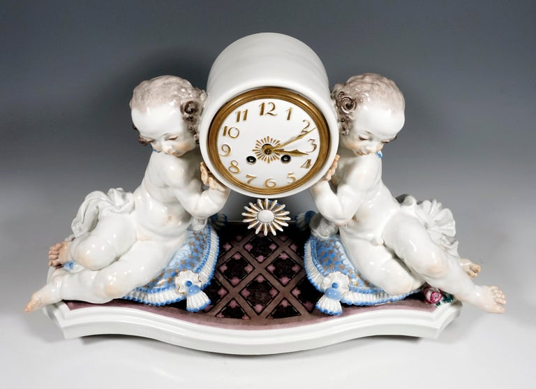 On a curved base plate with diamond pattern in marble look, sculptured cushions with tassel decoration, on the side seated figures, girl and boy, who gracefully carry the round clock case. White porcelain dial with applied Arabic numerals and hands